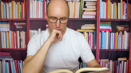 lampy : Serious man reading in the library. Close up view, concentrated teacher in glasses reading a book while sitting in front of bookshelves in the library. Table lamp evening late work
