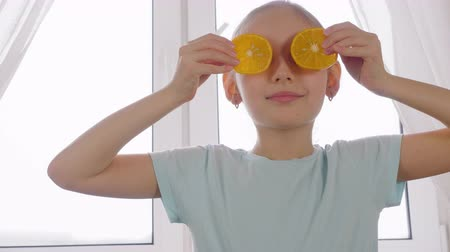tápláló : Cheerful girl teenager holding slices of fresh orange front eyes on kitchen window background. Happy girl holding fresh orange front face. Healthy lifestyle and fitness diet. Positive people emotion Stock mozgókép