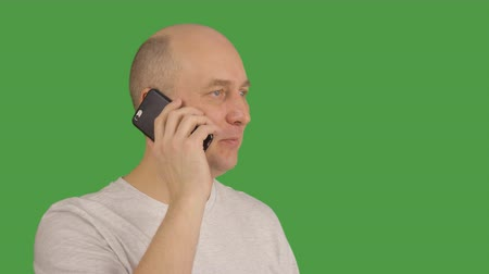 felicidade : White caucasian man in light grey t-shirt talking speaking by cell phone smartphone at transparent green screen alpha channel background. Portrait male adult joyfull man locked down close up. Stock Footage