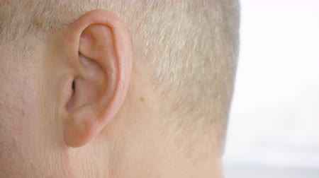 стрельба : Adult man with gray temples moving ear close up. Male ear macro shooting, side view. Otolaryngology and hearing health. Parts of human face and body. Health care concept