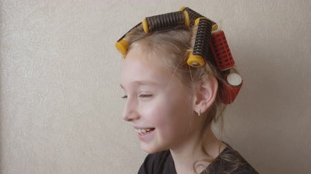 ondulação : Portrait smiling young girl with curlers on hair on light wall background. Joyful girl teenager while curling hair on rollers on copy space background. Beauty and hairstyle. Girl show tonque copyspace Vídeos