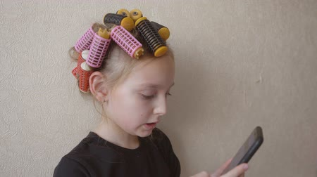 curling hair : Teenager girl with curlers on hair using smartphone on light wall background. Young girl with curler rollers on hair browsing mobile phone Stock Footage