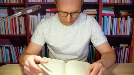 ansiklopedi : Focused man reading book carefully at table with lamp in evening home library. Serious man in glasses man read book in library on bookshelf background Stok Video