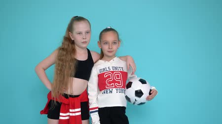 fotbalista : Los Angelos, California, USA - February 20 , 2019: teenager girl football fans in soccer uniform and ball posing on photo session. Girl cheerleaders on copyspace background Dostupné videozáznamy