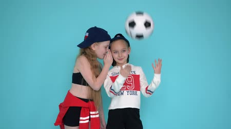 żart : Los Angelos, California, USA - February 20 , 2019: teenager girls in sportswear sport clothes stands at blue green background isolated. Girl hold football soccer ball. Girlfriend whishpers to ear girl