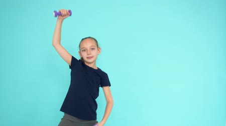 súlyzó : Cheerful girl teenager lifting dumbbells while aerobics gym on turquoise background in studio. Energy girl training with dumbbells at gym. Sport lifestyle fitness concept