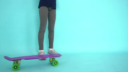 skate : Young girl teenager posing with skateboard in studio on turquoise background. Teenager girl training on longboard in studio. Youth sport and hobby isolated blue background