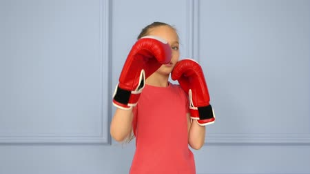boksör : Teenager girl in red boxing gloves training fight slow motion. Fitness teenager girl boxing in studio in coral tshirt. Boxing workout. Cardio exercises martial art box training
