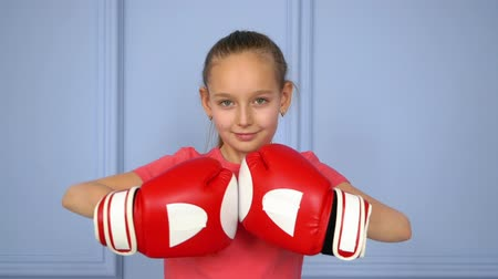 女性 : Portrait young girl boxer in boxing gloves ready to fighting on ring close up. Teenager girl preparing to boxing match slow motion. White boxer girl in red gloves pounding fists against each other 動画素材
