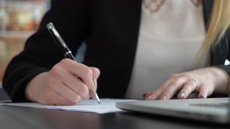 trançado : Closeup of womans hand writing on paper. Front view locked shot. Formal wear business woman black suit Stock Footage