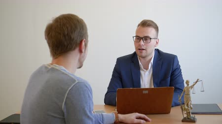 законодательство : Young jurist advising client in law office. Professional lawyer talking with customer in business office. Jurisconsult consulting in law office Стоковые видеозаписи