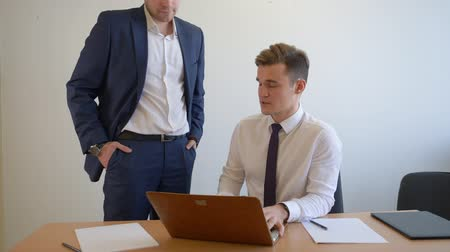 Войти : Business colleagues discussing and looking laptop at workplace in office. Business manager talking with boss about new project in modern office. Business people concept