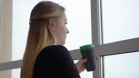 dyrektor : Business woman drinking coffee from cup and looking to window in office. Cheerful woman drinking coffee at beginning work day in office on window background