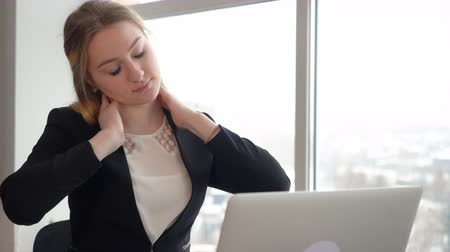 časová prodleva : Tired manager doing neck massage while hard work on laptop in business woman. Exhausted business woman working on notebook in office