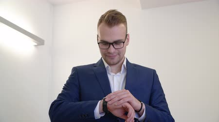 detalhes : Successful business man in eyeglasses and blue suit looking wrist watch in office. Portrait smiling businessman checking time on hand wristwatch