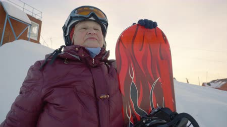 времяпровождение : Senior woman posing with snowboard on the mountain peak. Concentrated senior woman with snowboard on the mountain peak looking in front, before her ride down the snowy hill.