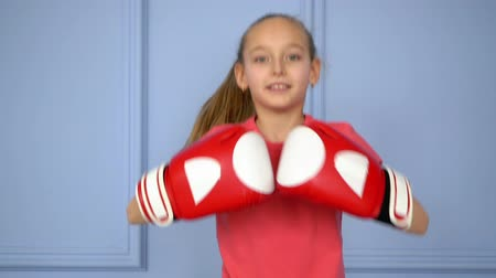 bokser : Cute little girl in boxing gloves. Front view beautiful young girl jumping while wearing boxing gloves. Sport concept Stockvideo
