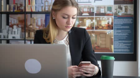 созерцать : Beautiful woman designer texting on her smartphone. Young attractive businesswoman using her smartphone while sitting at her working table with laptop and coffee. Young designer architect
