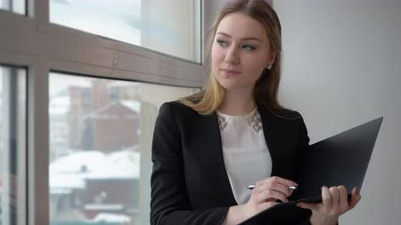 felnőtt : Beautiful entrepreneur making notes at her documents. Young and successful businesswoman making business notes while standing in front of a big window. Young woman analyst marketing accountant