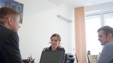 financial : Successful manager talking with his clients in the office. Happy lawyer and satisfied couple, the clients, taking the consults. Stock Footage