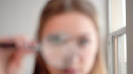 investigador : Woman looking on the magnifying glass. Womans eye through magnifying glass, close up macro. Portrait of cheerful young woman looking through magnifying glass