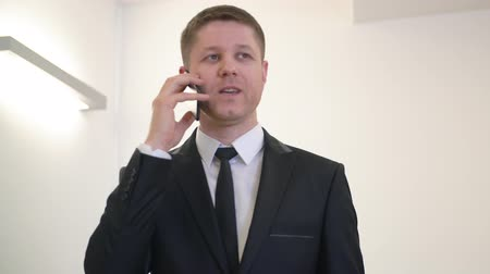 gadżety : Adult businessman talking on mobile phone. Successful businessman in black formal suit making business phone call on his smartphone. Business talks concept. Boss colling