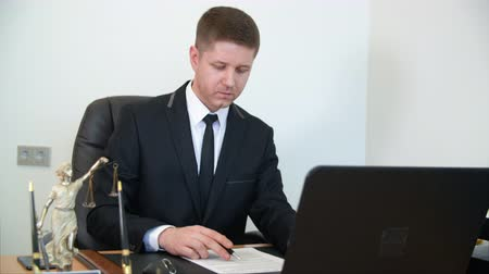 patron : Serious handsome businessman reading and signing contract. Young concentrated boss reading and signing business document while sitting at his working place. CEO boss chef patron working place Stock Footage