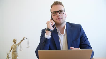 rechtvaardigheid : Confident lawyer making consultation by a smartphone. Young attractive lawyer in glasses and suit during phone call conversation with his client. Law consulting concept Stockvideo
