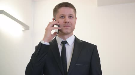 makler : Executive businessman using smartphone for mobile conversation in office. Portrait handsome man talking by mobile phone in business office. Business call concept