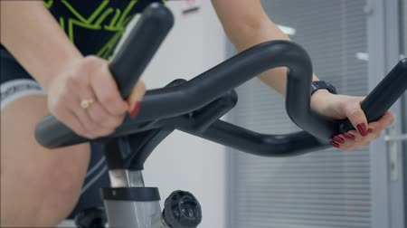 gevşek : Woman hands on the handlebars of the spin bike. Close up woman hands during the cycling workout in the gym. Stok Video