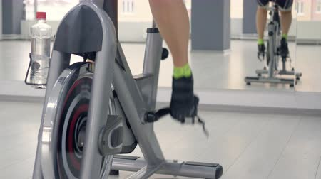 stationary : Woman feet spinning the indoor bike. Close up shot woman legs during cycling workout in front of the mirror. Close-up rear view feet rotation pedal and flywheel of static bike indoors gym