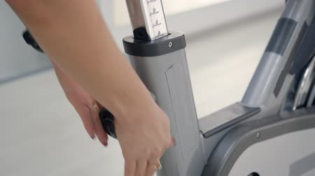 pino : Woman adjusting the seat on her spin bike. Close up shot woman hands adjusting seat on the static bike, woman preparing to workout.