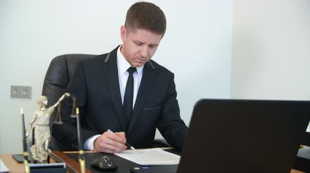 public worker : Lawyer at work. Young professional looks through the contract, puts a signature and stamp sitting at the table by the computer