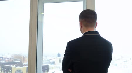 воротник : Businessman in suit looking on the cityscape out of the window in office. Back view young businessman standing in front of the window in the office.