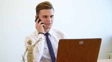 counsel : Handsome lawyer taking phone call at his working table. Close up view young successful lawyer speaking with his client on the mobile phone at the office.