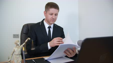 внимательный : Satisfied lawyer reading paper documents at his working table. Happy successful young lawyer attentive reading and checking paper documents, contract, at the office