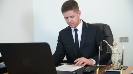 veredito : Professional lawyer reading and signing document on work table in law office. Man lawyer working with paper document and laptop on table in law firm