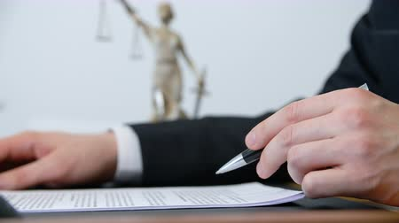 danışman : Close up hand of lawyer signing contract with pen at work table in lawyer office. Male hand signing document on justice goddess statue background in law firm Stok Video