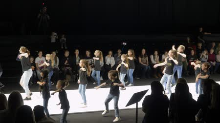 semana de moda : Moscow, Russia - March 21, 2019: teenagers dancing at performance stage on fashion show. Dancers performing on podium at fashion event Moscow Fashion Week. Stock Footage