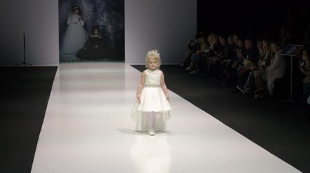 semana de moda : Moscow, Russia - March 21, 2019: little girl showing exclusive dress on podium at fashion event. Girl model walking on runway of fashion show at Moscow Fashion Week Stock Footage