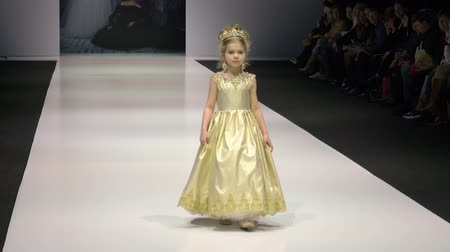 semana de moda : Moscow, Russia - March 21, 2019: little girl defiles in golden dress with shining diamond on podium at fashion show. Girl fashion model performing on glamour show at catwalk