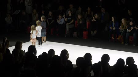 semana de moda : Moscow, Russia - March 21, 2019: children walking on catwalk at fashion show. Fashion model showing kid clothes collection on podium at fashion event Moscow Fashion Week