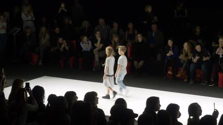 semana de moda : Moscow, Russia - March 21, 2019: couple teenager walking on runway at fashion show. Fashion model showing new clothes collection for teenager at fashion event. Moscow fashion week.