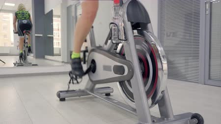 excesso de trabalho : Womans reflection in the mirror in tracksuit on a stationary bike. Legs are spinning pedals on the stationary bicycle. Back view.