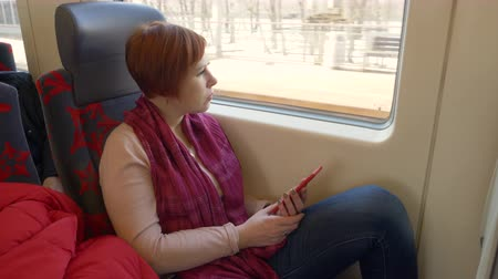 train workers : Traveling woman looking smartphone sitting on window background in moving train. Young woman riding in passenger train using mobile and looking to window