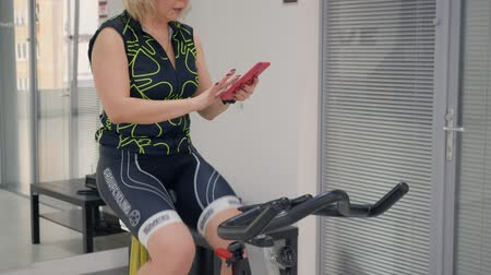 stationary : London, UK - March 12, 2019: sport woman spinning bike at cycling class and using smartphone. Fitness woman typing message on mobile while training bike exercise in health club Stock Footage
