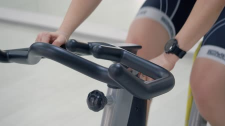 intenzivní : London, UK - March 12, 2019: female hand on handlebar on exercise bike while training. Sport woman wearing fitness bracelet while intensive cardio training on static bike