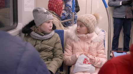 yüz buruşturma : Moscow, Russia - March 21, 2019: Two teenage girls in warm clothes rides the subway car sitting and talks each other.