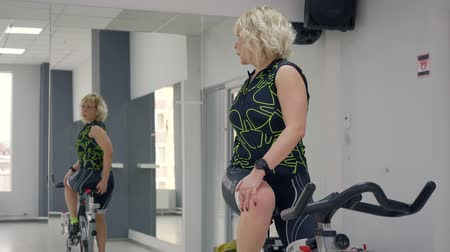 heart rate : London, UK - March 12, 2019: Caucasian woman with blond curles hair turn back to mirror for back stretch. Woman sits on static bike Stock Footage