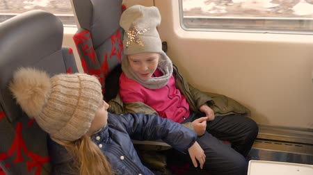 kruvazör : High angle shot of two happy girls traveling on train or bus and sitting on chairs. Young girls in winter clothes and knitted hat talk each other and laugh. High angle shot Stok Video